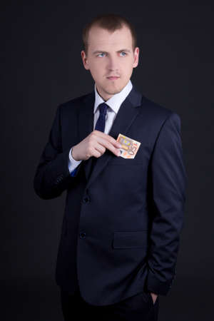 putting money in pocket: young man in business suit putting 50 euro banknote into pocket Stock Photo