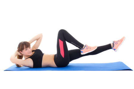 young woman doing exercises for abdominal muscles isolated on white background photo
