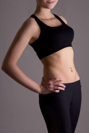 slim womans body in sports wear over grey background photo