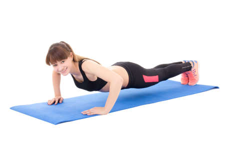 young beautiful woman doing push up exercise isolated on white background photo