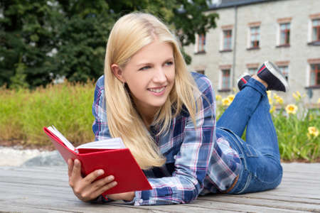 young beautiful woman lying in park with book photo