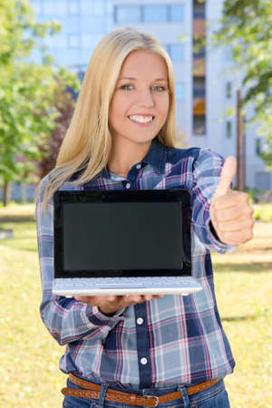 beautiful smiling woman with laptop thumbs up in park photo
