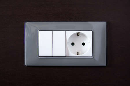 power outlet and light switch over wooden wall photo