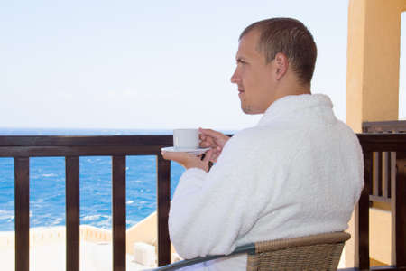young man sitting on balcony with cup of coffee photo