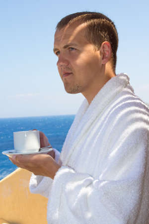 man in bathrobe with cup of coffee standing at terrace with sea view photo