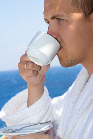 man in bathrobe drinking coffee on balcony with sea view photo
