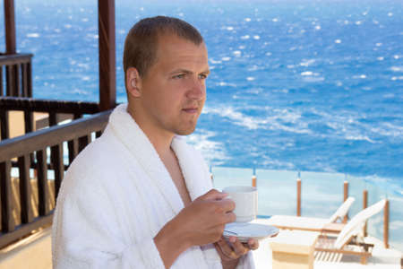 man in bathrobe with cup of coffee standing on balcony with sea view photo