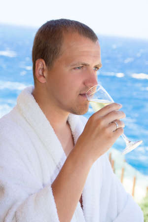 happy man in bathrobe drinking champagne on balcony with sea view photo