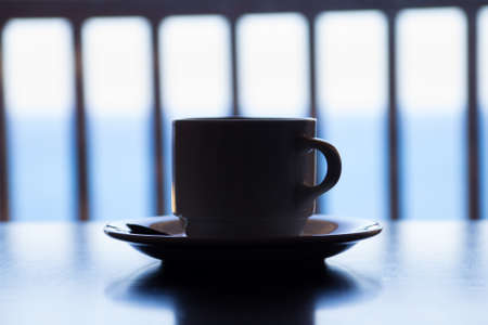 dark picture of cup of coffee on wooden table over sea view photo