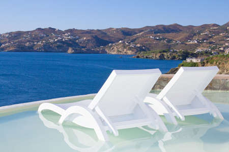 two white beach chairs in pool with beautiful sea view in Greece photo