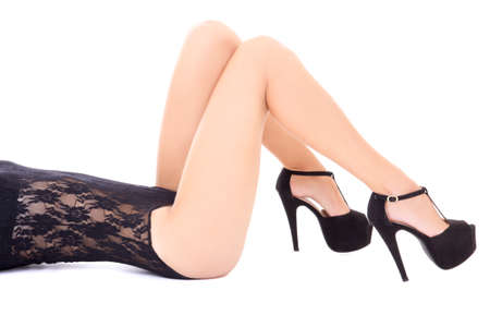 prostitution: female long legs in shoes on heels isolated on white background