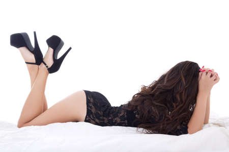 prostitute: silhouette of young charming woman in black lace lingerie lying on bed isolated on white background