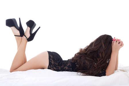 prostituta: silueta de mujer encantadora joven en ropa interior de encaje negro acostado en la cama aislado en el fondo blanco