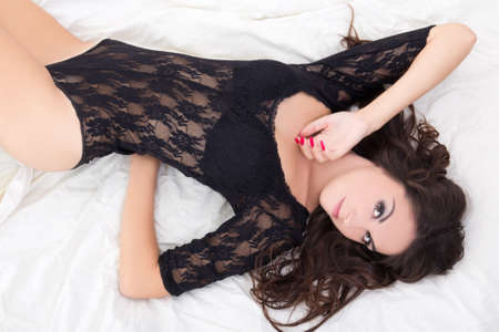young charming woman in black lace lingerie lying on bed photo