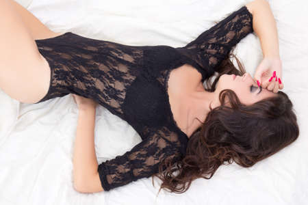 young beautiful seductive woman in black lace lingerie lying on bed photo