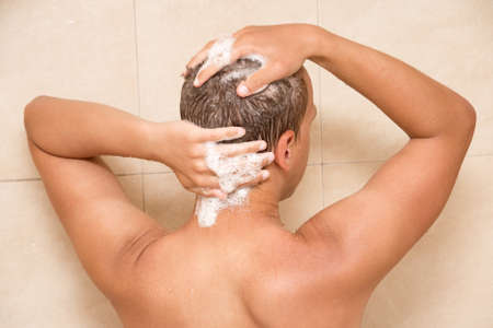 back view of young man washing his hair in shower photo
