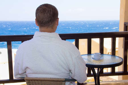 back view of man sitting on balcony with beautiful sea view photo
