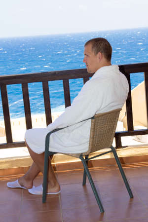 man sitting on balcony with beautiful sea view photo