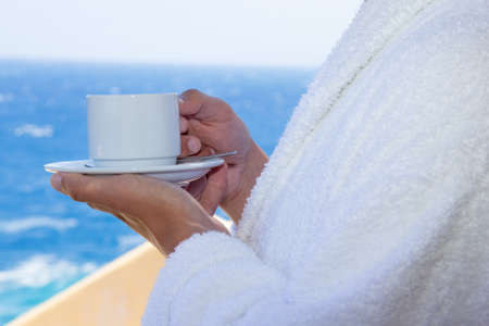 mug of coffee in male hands over sea view photo