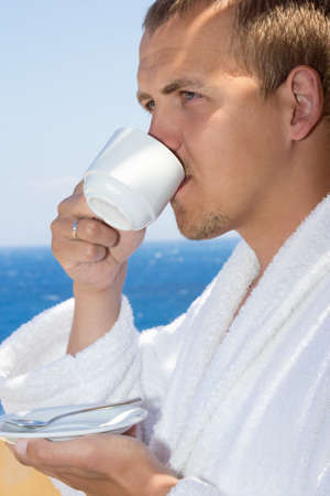 close up of man in bathrobe drinking coffee on balcony with sea view photo