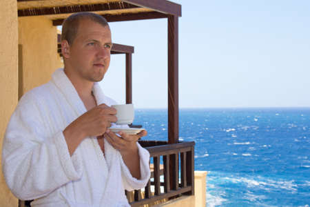 man in bathrobe with cup of coffee standing on balcony photo
