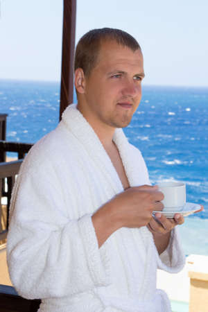 happy young man in bathrobe with cup of coffee standing on balcony photo