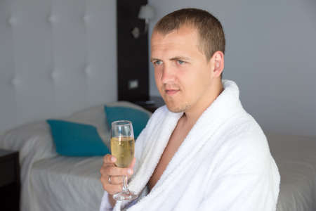 happy man in bathrobe drinking champagne in hotel room photo