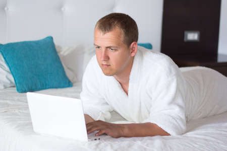 young handsome man in bathrobe using laptop in hotel room photo