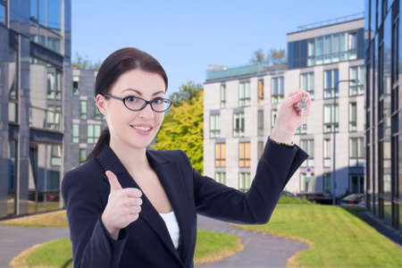 female real estate agent with key standing on street against modern building photo