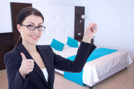 female real estate agent with key in modern flat photo