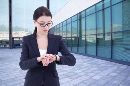 young business woman checks time on her wrist watch standing on street against modern office building