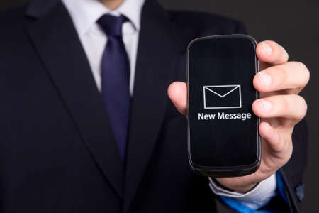 modern mobile phone with new message in business man hand photo