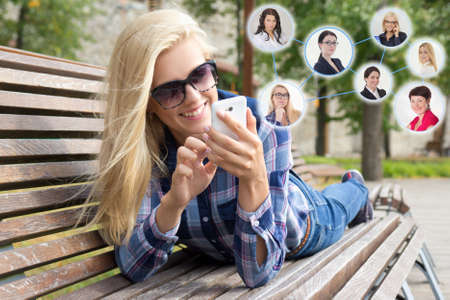 social network concept - beautiful woman using smartphone and icons with people portraits photo