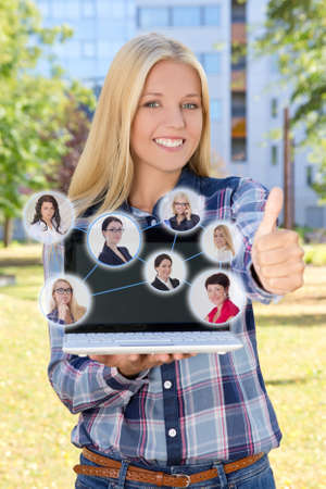 social network concept - beautiful smiling woman with laptop thumbs up in park photo