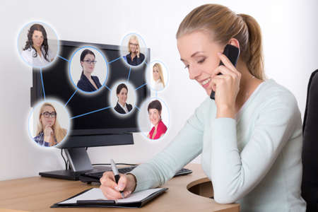 linked: social network concept - young businesswoman talking on the phone in office