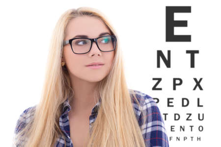 eye test: cute blondie girl in eyeglasses on the background of eye test chart Stock Photo