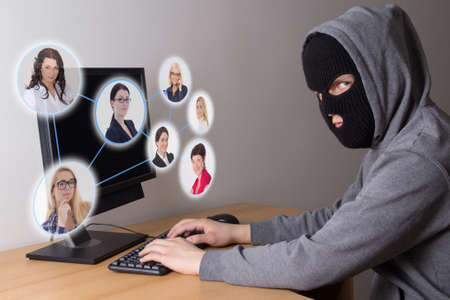 hackers: masked hacker stealing data from computers Stock Photo