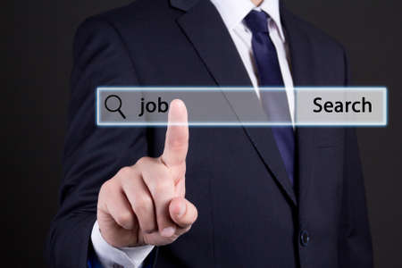 job search concept - businessman hand pressing an imaginary button over dark background photo