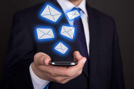 modern smart phone in business man hand and flying envelopes photo