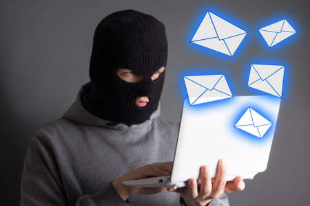 hacker in mask stealing data from laptop or sending spam messages photo