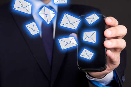 modern mobile phone with flying envelopes in business man hand photo