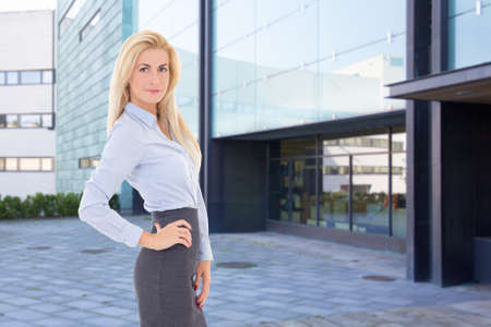 young beautiful blond business woman standing on street against office building photo