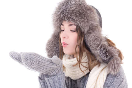 woman in winter clothes blowing something from her palms isolated on white background photo