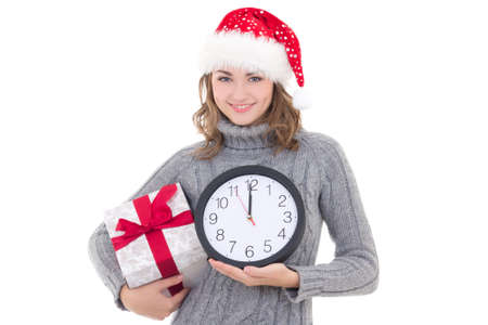 happy young beautiful woman in winter clothes and santa hat with christmas present and clock isolated on white background photo