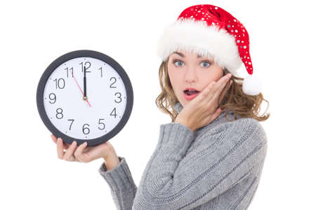 surprised beautiful woman in winter clothes and santa hat holding clock isolated on white background photo