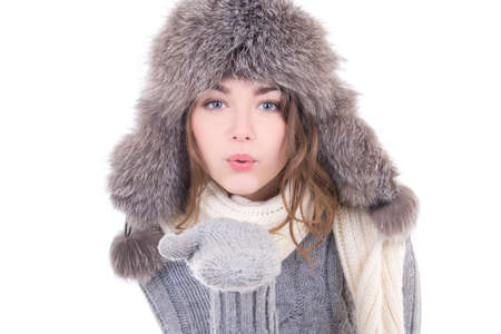 young woman in winter clothes blowing something from her palms isolated on white background photo