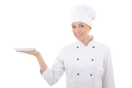 young woman chef  in uniform with empty plate isolated on white background photo
