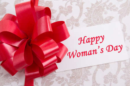 close up of gift box with big bow and greeting card with text Happy womans day photo