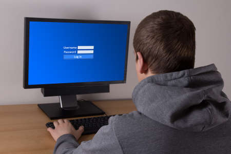 young man typing username and password in personal computer photo
