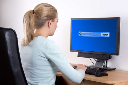 back view of woman searching something in internet with personal computer in office photo